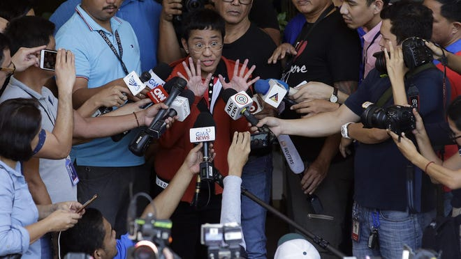 Rappler CEO and Executive Editor Maria Ressa, center, gestures as she talks to reporters after posting bail March 29, 2019.