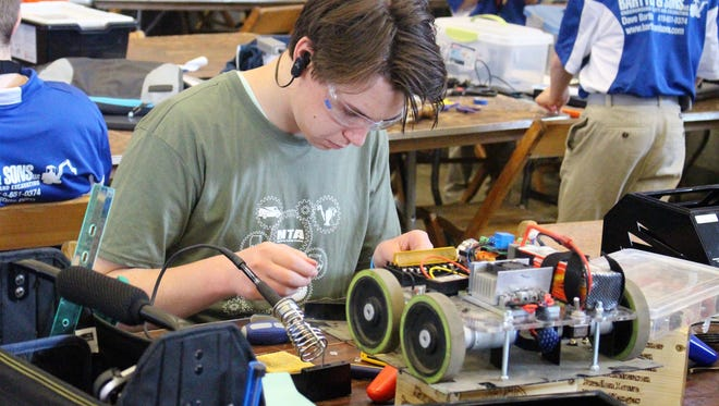 Dylan Kangas from Michigan inspects a small robot during the National Robotics Challenge on Friday.