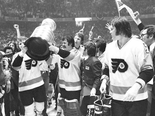 Flyers celebrate winning the Stanley Cup in Philadelphia, May 19, 1974. Center Bobby Clarke, left, and goalie Bernie Parent, right, hold the trophy as they celebrate.