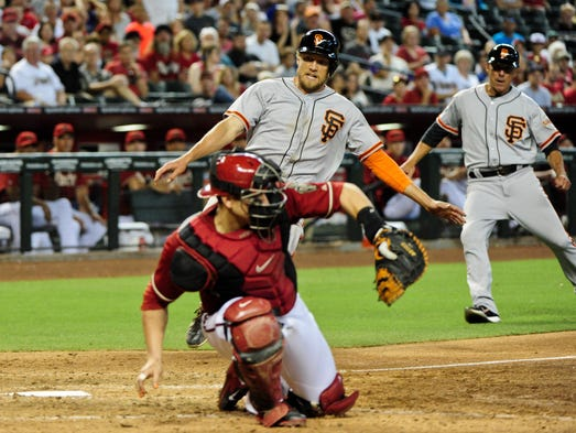 San Francisco Giants right fielder Hunter Pence (8) slides to score as Arizona Diamondbacks catcher Miguel Montero (26) catches the ball during the ninth inning at Chase Field on June 22, 2014.
