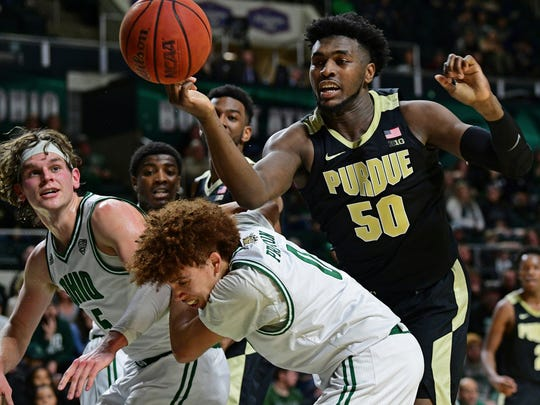 Purdue forward Trevion Williams (50) misplays a rebound against Ohio forward Ben Vander Plas, left, and guard Jason Preston, bottom, during the first half of an NCAA college basketball game, Tuesday, Dec. 17, 2019, in Athens, Ohio. (AP Photo/David Dermer)