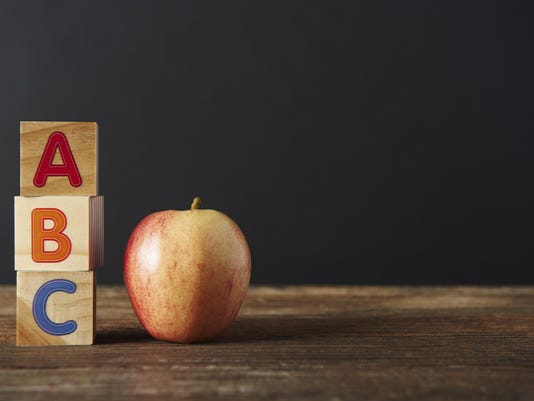 ABC Wooden spelling blocks and apple on wooden table
