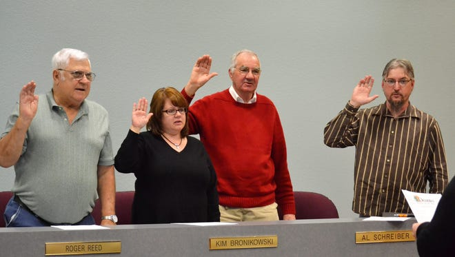 Oconto City Council members Roger Reed, Kim Bronikowski, Al Schreiber and Dean Reed take the oath of office from City Administrator at the re-organizational meeting of the City Council on April 17. Schreiber was elected council president, and Roger Reed vice president. All four and mayor Lloyd Heier were unopposed in the April 3 election.