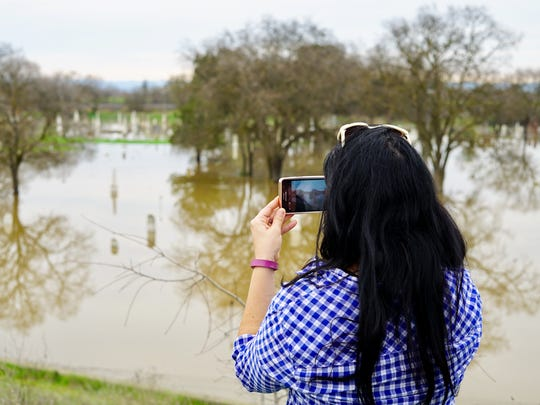 Amanda Abelar, an evacuee from Marysville, takes a picture of the flooded Marysville Cemetery on Wednesday Abelar said she planned to stay in Chico for a few more days before returning home for good.
