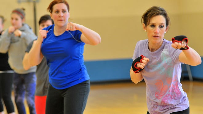 Carrie Hutton, right, and Laura Scudiere, do piloxing workout Tuesday, March 18, 2014, at the YMCA in downtown Wausau.