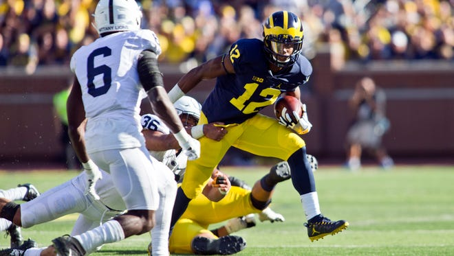 Michigan running back Chris Evans (12) escapes a tackle attempt from Penn State corner back Troy Shorts (36) and faces off against safety Malik Golden (6) in the second quarter at Michigan Stadium in Ann Arbor, Mich., Saturday. Michigan won, 49-10.