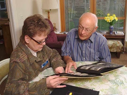 Linda Schmidt reviews old photos with Bell Tower resident Dean Berghammer.