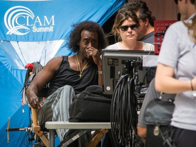 Star-director Don Cheadle looks at a monitor between