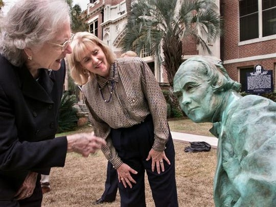 Two FSU supporters examine the statue of Francis Eppes, when it was unveiled in 2002 at FSU's Westcott Hall. Eppes, the grandson of Thomas Jefferson, was a Tallahassee mayor and founder of the 19th century seminary that became Florida State University.