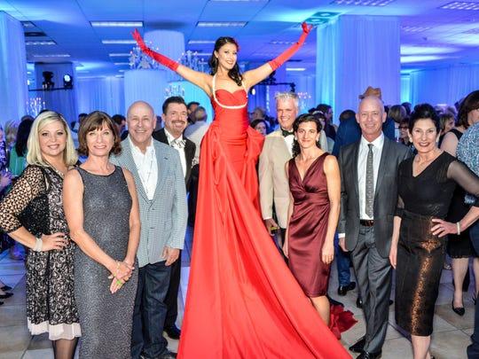 (l to r) Lisa Vossler Smith, Lise Baadh, Gary Johns, Mark Davis, (Red Dress Model), William Kopelk, Regina Basterrechea O'Donnell, J. Chris Mobley, Maureen Erbe.