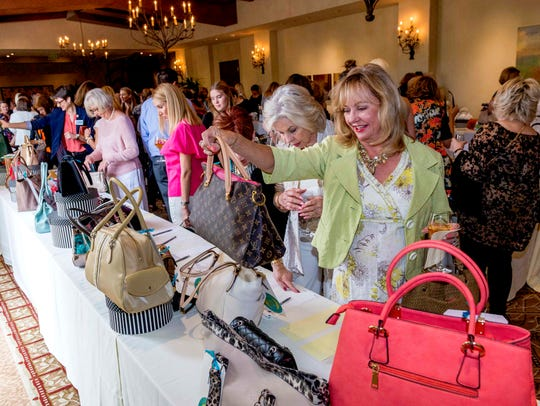 Gayle Hodges, right, admires a silent auction offering at the Old Bags Luncheon, a benefit for CancerPartners, in March 2018.