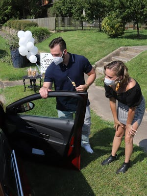 Coady Wooten, left, and his fiancee, Jessye King, pass out doughnut hole kebabs as they greet guest, Thursday, August 6, 2020, at their drive-thru-wedding shower in the Belle Grove Historic District on N 6th Street. King said that the COVID-19 pandemic caused the Fort Smith couple to change a few of the details of their August 8, 2020, wedding but it's not stopping them from getting married.
