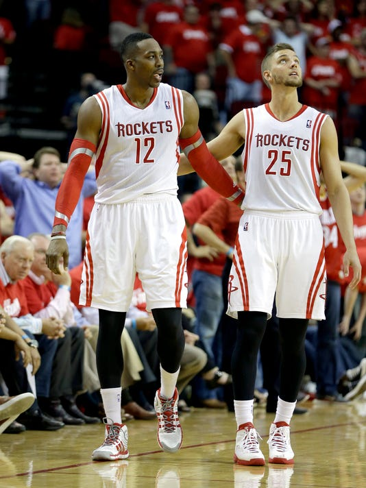 """FILE - In this April 20, 2014, file photo, Houston Rockets' Chandler Parsons (25) puts his arm around Dwight Howard (12) after Howard fouled out of the game during overtime in Game 1 of an opening-round NBA basketball playoff series against the Portland Trail Blazers in Houston. Howard says the departure of Parsons won't have an """"affect"""" on the Rockets' title hopes next season. (AP Photo/David J. Phillip, File)"""