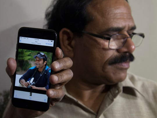 A man shows a picture of Alok Madasani, an engineer