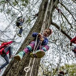 Autumn Shafer, 8, joins other children from all over central Ohio in climbing a tree using ropes at the Arbor Day Festival at Dawes Arboretum.