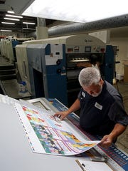 Chris Stewart checks on the quality of a print coming off the press  at Truax Printing's Ashland plant.