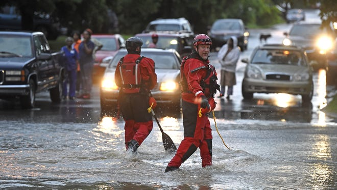 Members of the OEM swift water team check the water level before letting cars cross flooded waters in North Nashville on Ewing Creek at the corner of Gwynwood Drive and Ewingdale Thursday in Nashville.