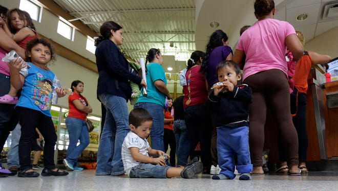 Immigrants who entered the U.S. illegally stand in line at the bus station after they were released from a Customs and Border Protection processing facility in McAllen, Texas, in June.