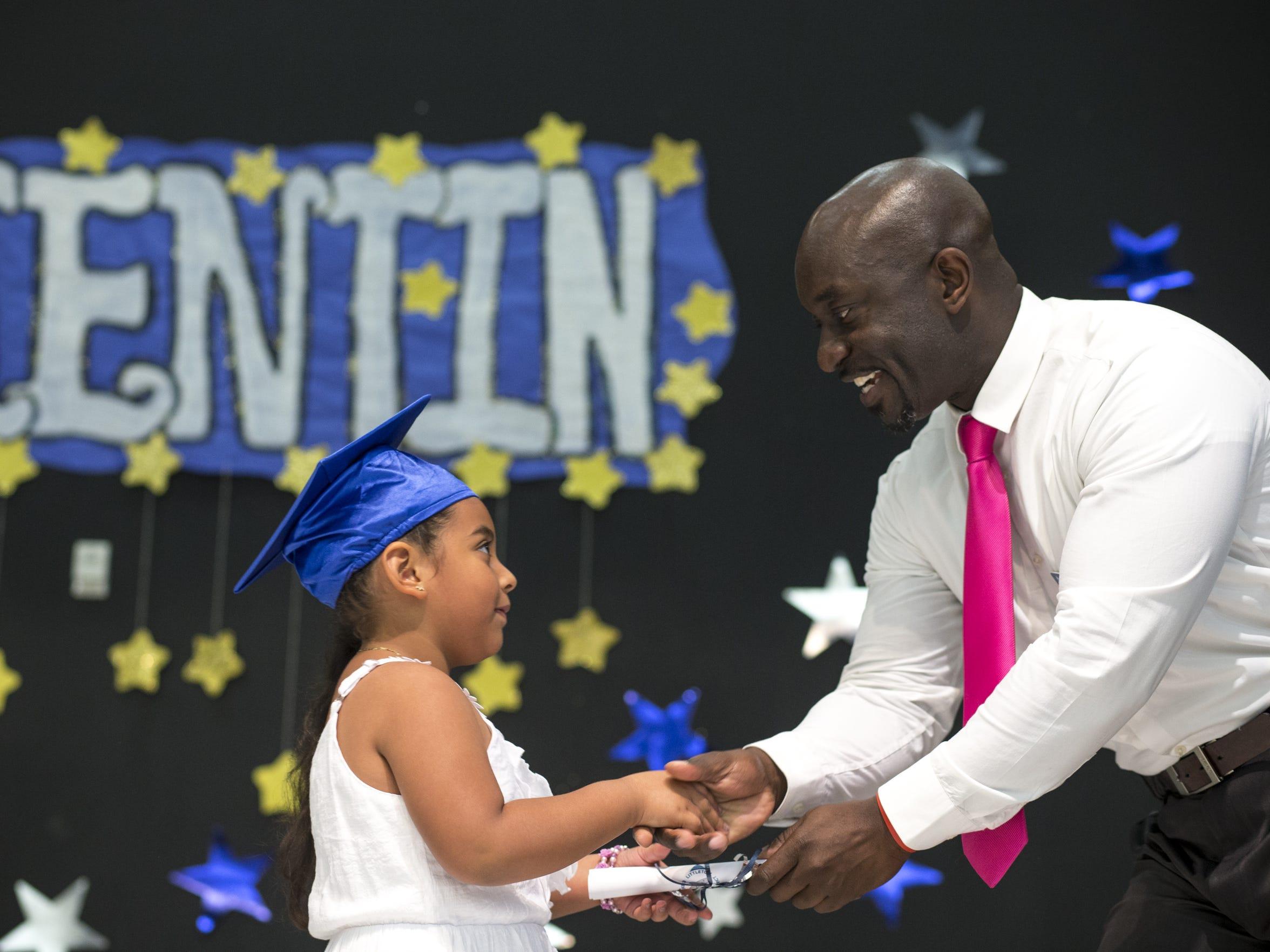 Principal Eric Atuahene presents Jenneyra Ceja Granados with her diploma during kindergarten promotion.