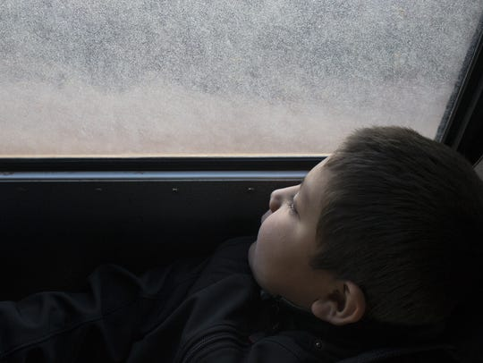 Marston Tso looks out the window of a school bus during