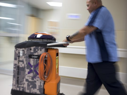 "VA tech Ross Estrella pushes a germ-killing robot dubbed ""Chief"" down the hall at the Phoenix VA Medical Center on Sept. 14, 2016."