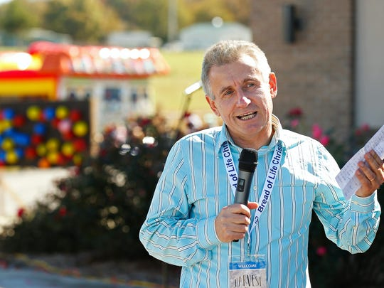 Lead pastor Mykola Illyuk talks to attendees during Bread of Life Christian Church's Russian Harvest Festival at the church grounds in Rogersville, Mo. on Oct. 22, 2016.