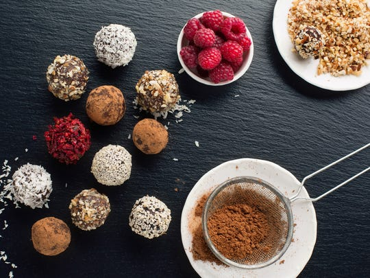 Homemade chocolate and nut candy balls with cocoa powder, coconut, berries and chopped hazelnuts.