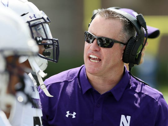Northwestern Wildcats head coach Pat Fitzgerald talks to his players on the sidelines in the first half of their game against the Duke Blue Devils at Wallace Wade Stadium.