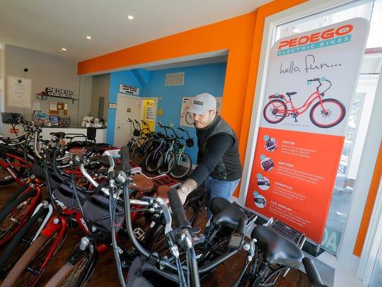 Adam Levine, owner of Pedego Electric Bikes, displays