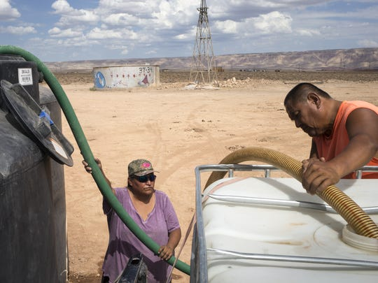 Paul Lincoln, right, and Glenda Seweingyawma pump water