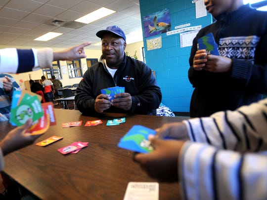 Derrick Eddings, center, plays a hand of Old Maid with a group of children Wednesday afternoon at the YWCA off French Broad Avenue. Eddings has been working with the YWCA's after school and day care programs for years.