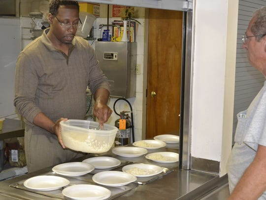 Pastor Manuelus Reacco served food to guests at Transformation