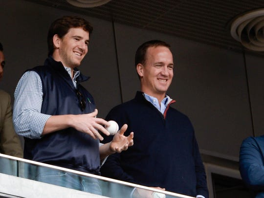 New York Giants quarterback Eli Manning and Denver Broncos quarterback Peyton Manning watch the game between the New York Yankees and Tampa Bay Rays at Yankee Stadium, May 4, 2014.