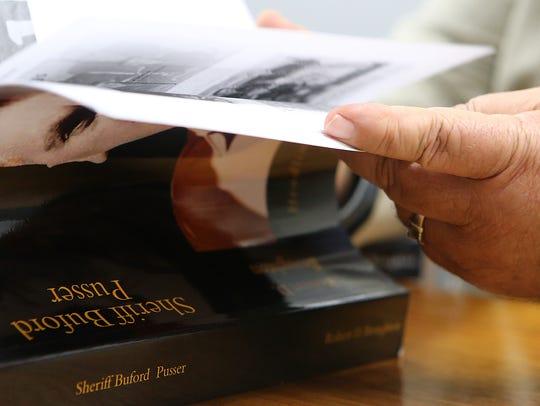 Author Robert D. Broughton flips through his book 'Sheriff