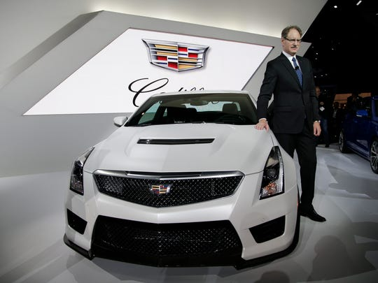 Cadillac President Johan de Nysschen poses for photos with the Cadillac 2016 ATS-V coupe at the Los Angeles Auto Show.