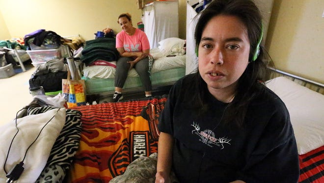 Tiffany Alberti, originally of San Antonio sits on her bed inside the women's dormitory at the Opportunity Center for the Homeless at 1298 Myrtle Monday. She has been a resident of the facility for 2 years. Behind her is fellow resident Alexandra Serrano.