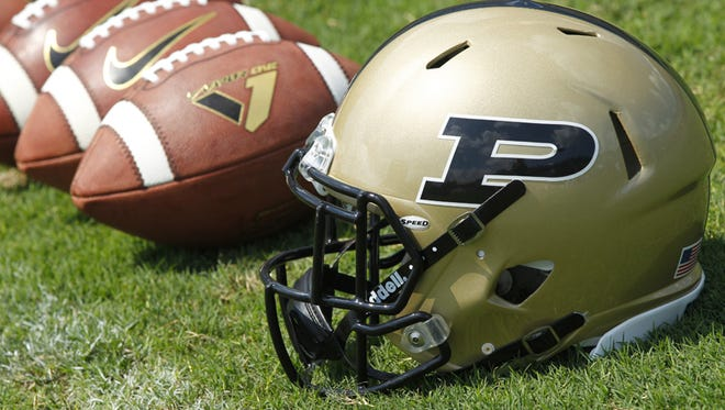 A helmet is lined up with several footballs during Purdue football media day Sunday, August 11, 2013, at Ross-Ade Stadium on the campus of Purdue University.