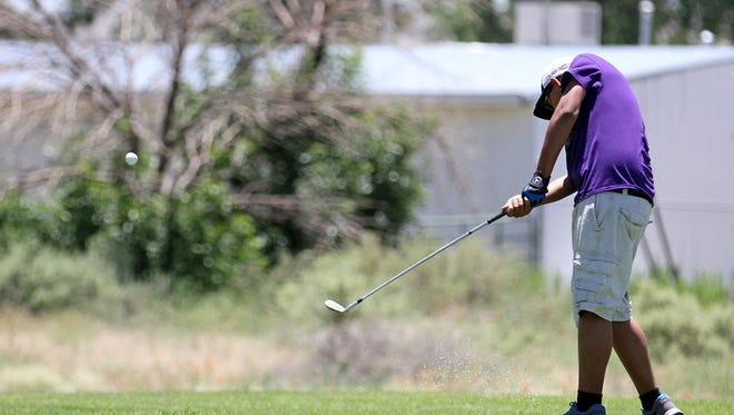 Luis Camacho, 13, of Kirtland, hits at the first tee, Thursday, June 18, 2015, during first tee golf lessons at Riverview Golf Course in Kirtland.