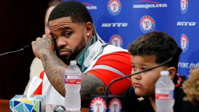 Ex-Tiger Prince Fielder, left, wipes his eyes as he sits by his son Haven during a news conference in Arlington, Texas.