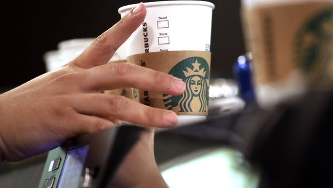 Barista reaches for an empty cup at a Starbucks