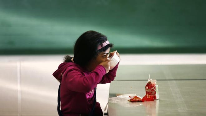 8:59 a.m.: Second-grader Sarah Alaragi, 8, finishes off her breakfast before school starts at School 109 on Thursday, March 18, 2010. Eighty-six percent of students at the elementary school are eligible for free and reduced lunches because of poverty. Those students also receive a free breakfast, often cereal and milk. Education researchers have pegged poverty as one of the most serious predictors of low educational achievement.