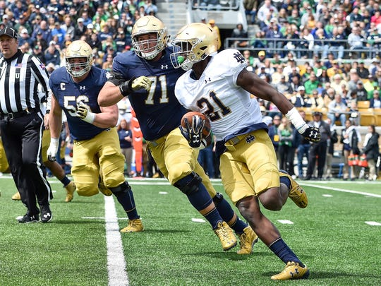 Notre Dame Fighting Irish safety Jalen Elliott (21) is chased by offensive lineman Alex Bars (71) after Elliott intercepted a pass in the first quarter of the Blue-Gold Game at Notre Dame Stadium.