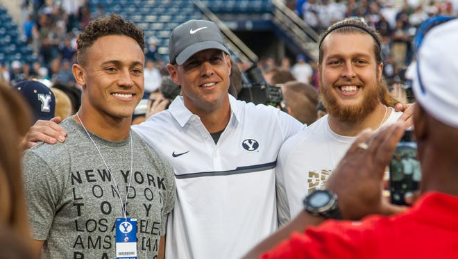 Former Southern Utah players Miles Killebrew (left) and James Cowser (right) pose for a photo with former coach Ed Lamb after Saturday's game against Brigham Young in Provo, Utah, Nov. 12, 2016.