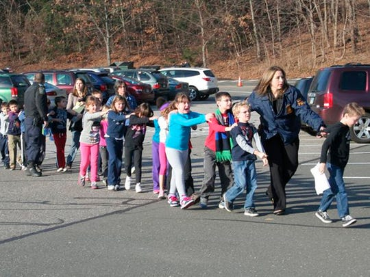 State police personnel lead children from Sandy Hook Elementary School in this picture from the Newtown Bee, in Newtown, Conn, on  December 14, 2012.
