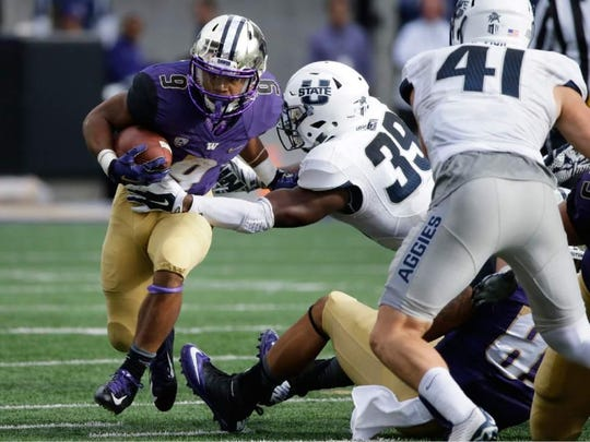 Washington's Dwayne Washington looks to break a tackle against Utah State during the first half of an NCAA college football game. Washington won 31-17.