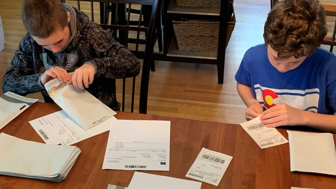 Dedham residents can walk, run or bike in the Social Distance 5K to benefit Dedham residents coping with the economic impact of COVID-19. Pictured are members of the Rotchford family making and sending masks.