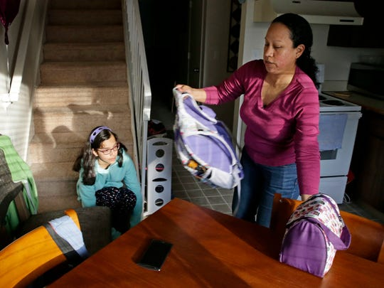 In this photo taken March 31, 2016, Teresa Garcia, right, helps her daughter, Alondra Miranda, 11, get ready for school at their home in Federal Way, Wash., south of Seattle. Garcia, who has spent 14 years in the United States illegally after staying beyond the expiration of her tourist visa in 2002, is one of millions who could be affected when the political fight over immigration comes to the U.S. Supreme Court on Monday, April 18, 2016 as the court weighs the fate of Obama administration programs that could shield roughly 4 million people from deportation and grant them the legal right to hold a job.