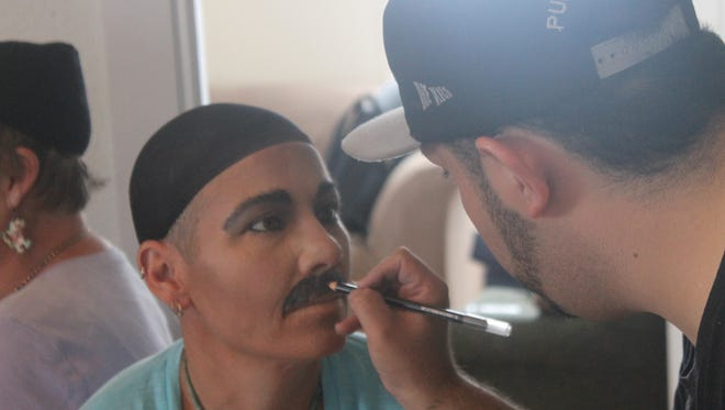 """Angel Montanez drawis a mustache on Dr. Emma so that she will look like Queen frontman Freddie Mercury during the """"Life is a Drag"""" event at WNMU over the weekend."""
