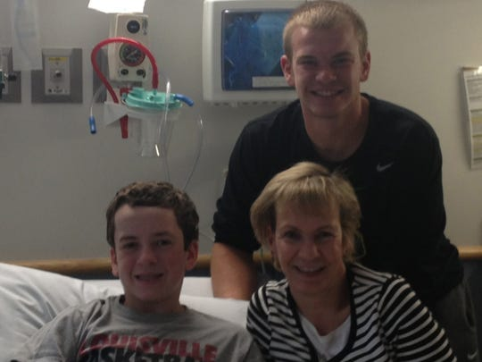 Patrick McSweeney, left, with his mother Debbie and his brother, Alex