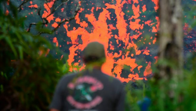 A man watches as lava slowly bubbled into neighborhoods  near the Leilani Estates in Hawaii